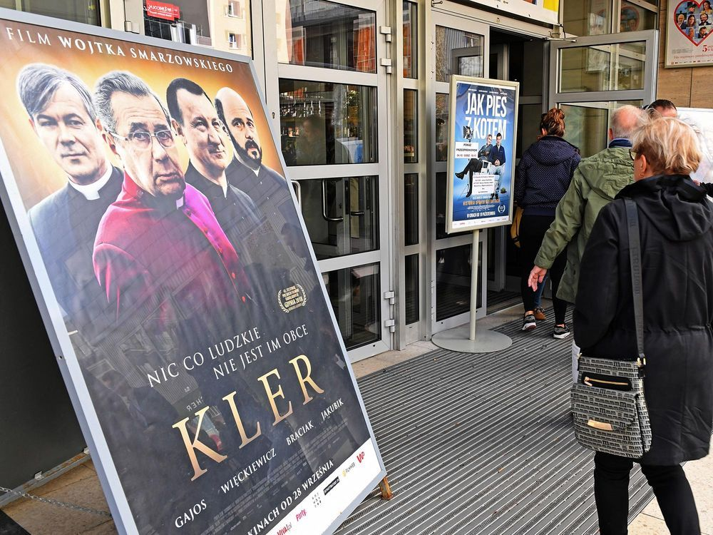 cinema goers pass a kler film poster in warsaw