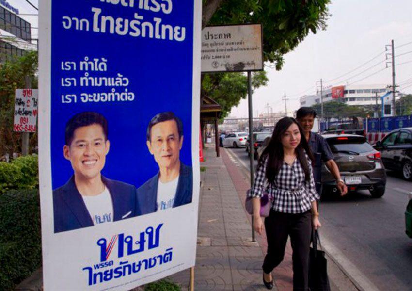 pejalan kaki berjalan melewati poster pemilu yang mempromosikan anggota partai politik thailand raksa chart di bangkok thailand pada rabu
